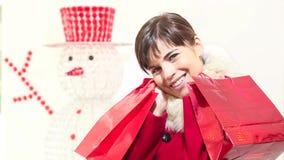 Mujer de la Navidad con los bolsos rojos, sonrisas, concepto que hace compras almacen de metraje de vídeo