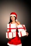 Mujer de la Navidad del sombrero de Papá Noel que sostiene los regalos de la Navidad Fotos de archivo libres de regalías