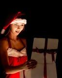 Mujer de la Navidad del sombrero de Papá Noel que sostiene los regalos de la Navidad Imagen de archivo libre de regalías