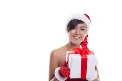 Mujer de la Navidad del sombrero de Papá Noel que sostiene los regalos de la Navidad que sonríen con g Fotos de archivo