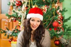 Mujer de la Navidad en el sombrero de Papá Noel que celebra Año Nuevo en casa Foto de archivo