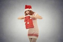 Mujer de la Navidad en el sombrero rojo de Papá Noel que sostiene el bolso del regalo de la abertura Fotos de archivo
