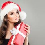 Mujer de la Navidad en Santa Hat con la caja de regalo roja de Navidad Imagen de archivo