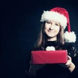 Mujer de la Navidad en Santa Hat con la caja de regalo roja Fotos de archivo libres de regalías