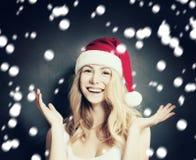 Mujer de la Navidad en Santa Hat Having Fun en nieve Foto de archivo libre de regalías