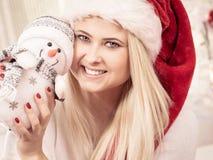 Mujer de la Navidad plaing con el juguete del muñeco de nieve Foto de archivo libre de regalías
