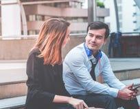 Mujer de la oficina con el amante del hombre de negocios que habla ligando la sentada al aire libre foto de archivo