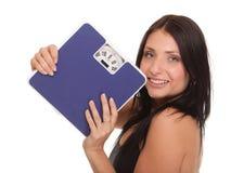 Mujer de la pérdida de peso en la escala feliz Fotos de archivo