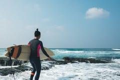 Mujer de la persona que practica surf con la tabla hawaiana imagen de archivo libre de regalías