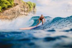 Mujer de la persona que practica surf en el paseo de la tabla hawaiana en ola oceánica Mujer en el océano durante practicar surf Fotografía de archivo libre de regalías
