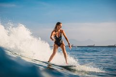 Mujer de la persona que practica surf en el paseo de la tabla hawaiana en ola oceánica Mujer en el océano durante practicar surf  imagen de archivo