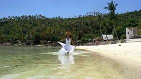 Mujer de la playa que corre cerca del agua en vestido largo y el sombrero blancos que disfrutan de la libertad durante viaje de l almacen de metraje de vídeo