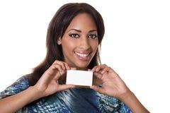 Mujer de la raza mezclada que sostiene una tarjeta de visita en blanco. fotografía de archivo