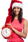 Mujer de la raza mixta en el sombrero de santa con el despertador Fotografía de archivo
