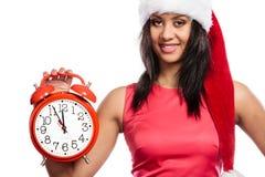 Mujer de la raza mixta en el sombrero de santa con el despertador Imágenes de archivo libres de regalías