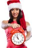 Mujer de la raza mixta en el sombrero de santa con el despertador Fotografía de archivo libre de regalías