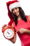 Mujer de la raza mixta en el sombrero de santa con el despertador Imagen de archivo