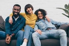 mujer de la raza mixta que abraza a dos amigos masculinos sonrientes imagenes de archivo