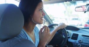 Mujer de la raza mixta que habla en el coche con los auriculares Imagen de archivo