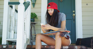 Mujer de la raza mixta que se sienta en el pórtico con mandar un SMS del monopatín Imagen de archivo libre de regalías