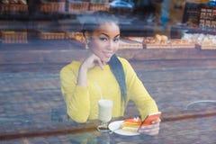 Mujer de la raza mixta que se sienta en una cafetería con su bebida del latte Foto de archivo libre de regalías