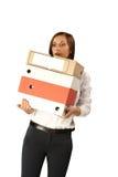 Mujer de la secretaria con una pila grande de carpetas aisladas en el fondo blanco Imagen de archivo libre de regalías