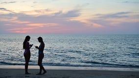 mujer de la silueta 4K que comprueba medios sociales en el teléfono elegante en la playa