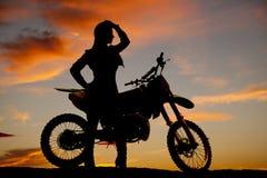 Mujer de la silueta por la cabeza de la mano de la bici de la suciedad Imagen de archivo