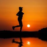 Mujer de la silueta que corre contra puesta del sol anaranjada Fotografía de archivo
