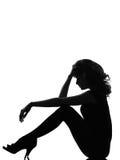 Mujer de la silueta que sienta pensativo triste Imagen de archivo
