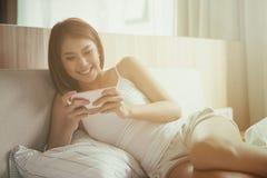 Mujer de la sonrisa de los jóvenes que juega el teléfono elegante que miente en la cama en casa Imagen de archivo libre de regalías