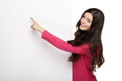 Mujer de la sonrisa de los jóvenes que señala en un tablero en blanco Fotografía de archivo libre de regalías