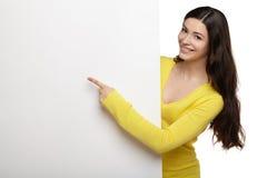 Mujer de la sonrisa de los jóvenes que señala en un tablero en blanco Foto de archivo