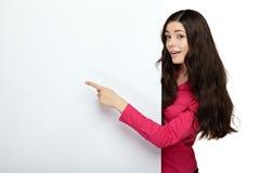 Mujer de la sonrisa de los jóvenes que señala en un tablero en blanco Imagenes de archivo