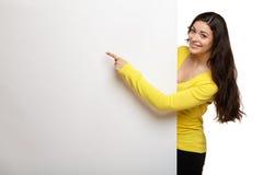 Mujer de la sonrisa de los jóvenes que señala en un tablero en blanco Fotos de archivo libres de regalías