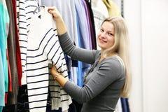 Mujer de la sonrisa en tienda de la ropa Imagen de archivo