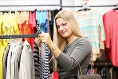 Mujer de la sonrisa en tienda de la ropa Imagenes de archivo