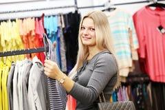 Mujer de la sonrisa en tienda de la ropa Imágenes de archivo libres de regalías