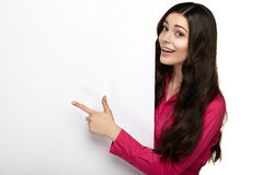 Mujer de la sonrisa que se coloca punteaguda su finger en el tablero Foto de archivo