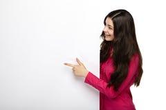 Mujer de la sonrisa que se coloca punteaguda su finger en el tablero Fotografía de archivo libre de regalías