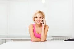 Mujer de la sonrisa que usa la tabla que se sienta de la llamada de teléfono Imagen de archivo libre de regalías