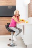 Mujer de la sonrisa que usa la tabla que se sienta de la llamada de teléfono Imágenes de archivo libres de regalías