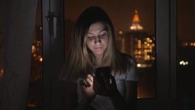 Mujer de la tarde que se coloca con ella de nuevo a la ventana y a las aplicaciones Smartphone almacen de video