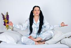 Mujer de la yoga en cama Foto de archivo libre de regalías