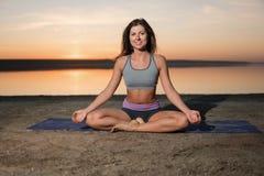 Mujer de la yoga en la playa en la puesta del sol imagenes de archivo