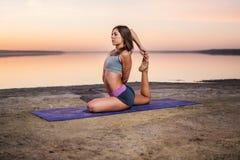 Mujer de la yoga en la playa en la puesta del sol fotos de archivo