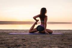 Mujer de la yoga en la playa en la puesta del sol foto de archivo libre de regalías