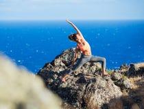 Mujer de la yoga que practica en una playa fotografía de archivo