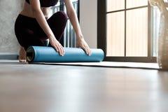 Mujer de la yoga que rueda su estera de la lila después de una clase de la yoga Fotografía de archivo libre de regalías