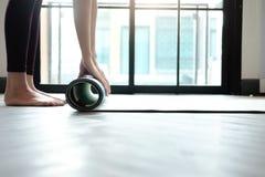 Mujer de la yoga que rueda su estera de la lila después de una clase de la yoga Imágenes de archivo libres de regalías